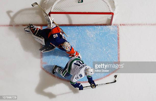Mason Raymond of the Vancouver Canucks scores a shootout goal past goaltender Kevin Poulin of the New York Islanders on January 11 2011 at Nassau...