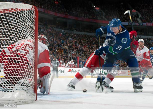 Mason Raymond of the Vancouver Canucks shoots the puck at Jimmy Howard of the Detroit Red Wings during their NHL game at Roger s Arena December 21...