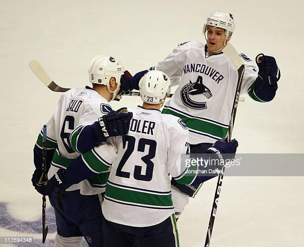 Mason Raymond of the Vancouver Canucks skates in to join teammates Alexander Edler and Sami Salo for a celebration after Salo's 1st period goal...