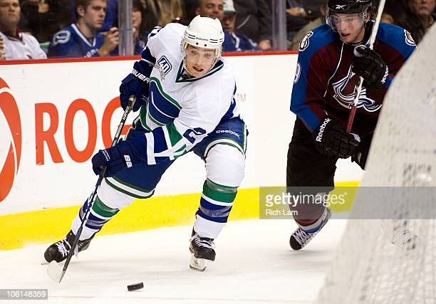 Mason Raymond of the Vancouver Canucks tries to control the loose puck while being pursed by Matt Duchene of the Colorado Avalanche during the third...