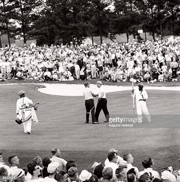 Mason Rudolf congratulates Jack Nicklaus after sinking putt on the 18th hole with caddie Willie Peterson during the 1965 Masters Tournament at...
