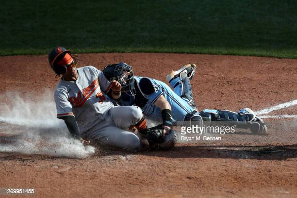 Mason Williams of the Baltimore Orioles is tagged out at home plate by Danny Jansen of the Toronto Blue Jays on a throw from Teoscar Hernandez of the...