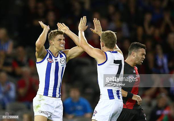 Mason Wood of the Kangaroos celebrates after kicking a goal with Jack Ziebell of the Kangaroos as Ryan Crowley of the Bombers looks dejected during...