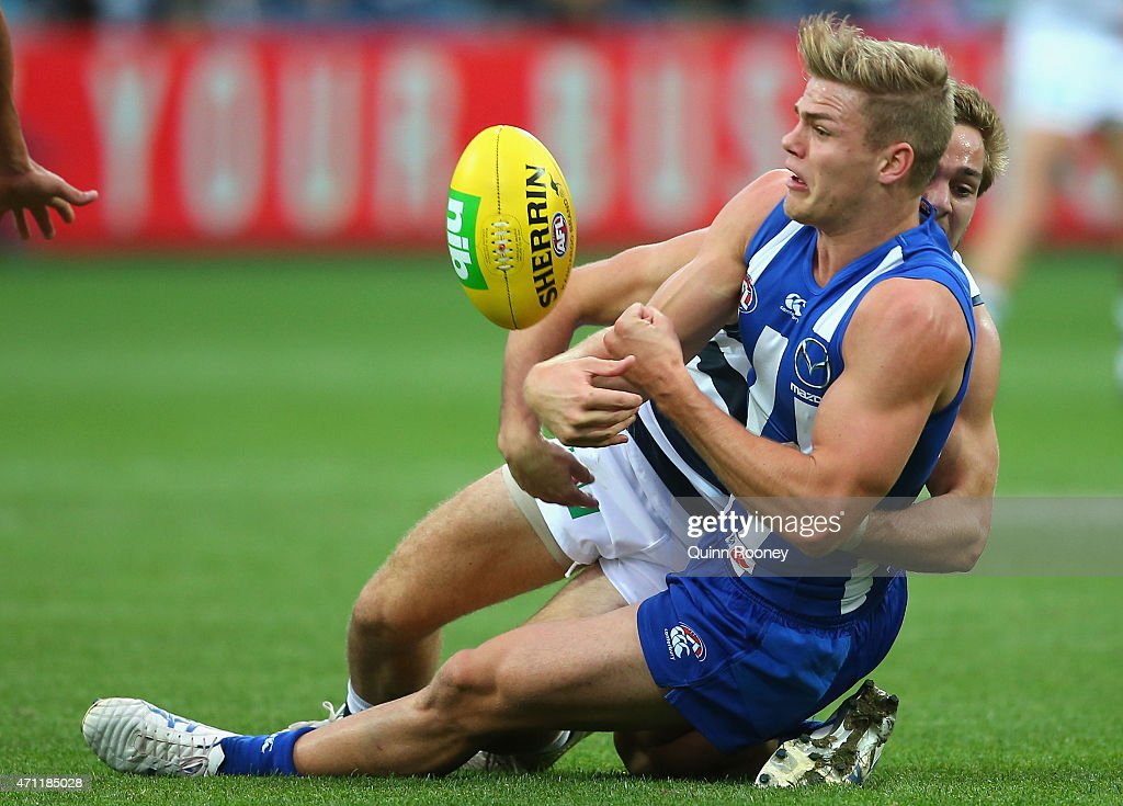 Mason Wood of the Kangaroos handballs whilst being tackled by Cory Gregson of the Cats during the round four AFL match between the Geelong Cats and the North Melbourne Kangaroos at Simonds Stadium on April 26, 2015 in Geelong, Australia.