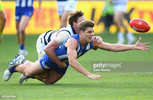 Mason Wood of the Kangaroos is tackled by Jed Bews of the Cats during the round 12 AFL match between the Geelong Cats and the North Melbourne...