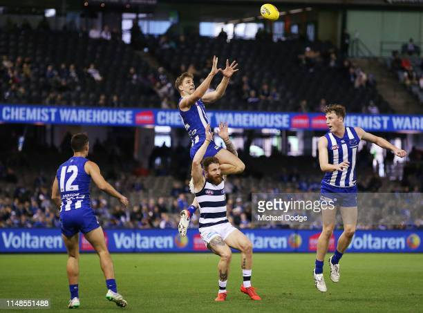 Mason Wood of the Kangaroos marks the ball high over Zach Tuohy of the Cats during the round eight AFL match between the North Melbourne Kangaroos...