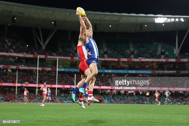 Mason Wood of the Kangaroos takes a mark over Zak Jones of the Swans during the round seven AFL match between the Sydney Swans and the North...