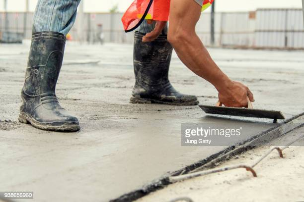 mason worker leveling concrete with trowels mason hands spreading poured concrete - cement stock pictures, royalty-free photos & images