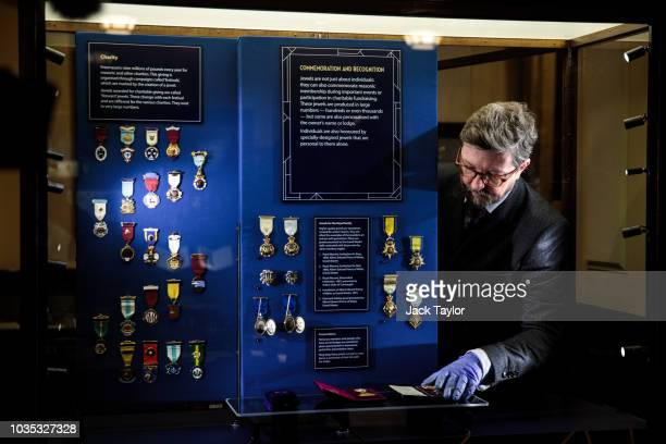 Masonic jewels are placed back into a display cabinet during a press preview at the Museum of Freemasonry on September 18 2018 in London England The...
