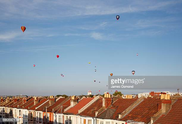 mass ascent of hot air balloons over rooftops - bristol england stock pictures, royalty-free photos & images