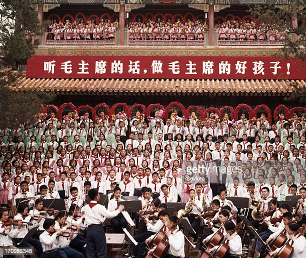 A mass chorus formed by peking children singing the revolutionary song 'we are successors to communism' at chingshan park in celebration of...