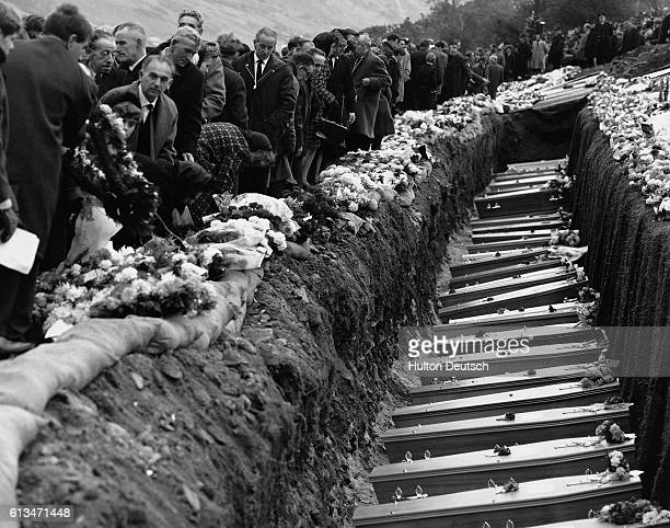 A mass grave filled with coffins on the mountainside above the Welsh mining village of Aberfan 1966 A mass funeral was held for 81 of the 116...