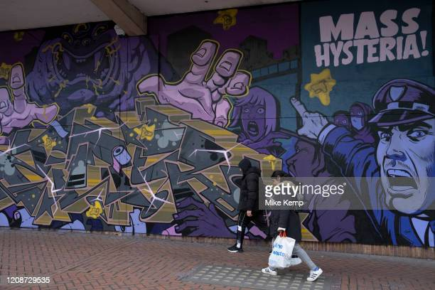 Mass hysteria street art graffiti on boarded up shops which are closed in Birmingham city centre due to the Coronavirus outbreak on 31st March 2020...