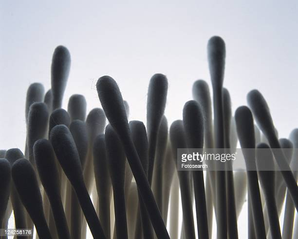 Mass of cotton swabs, front view, close up, colored background