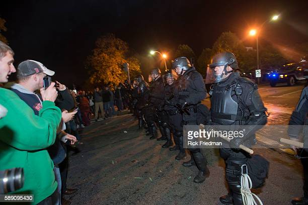 Mass State Police in riot gear move the crowd from around Fenway Park as fans celebrate the Boston Red Sox defeating the St Louis Cardinals to win...