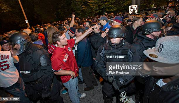 Mass State Police in riot gear move the crowd from around Fenway Park as fans celebrate the Boston Red Sox winning the World Series just outside...