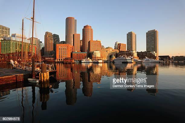 USA, Massachusetts, Boston, City waterfront reflected in harbor