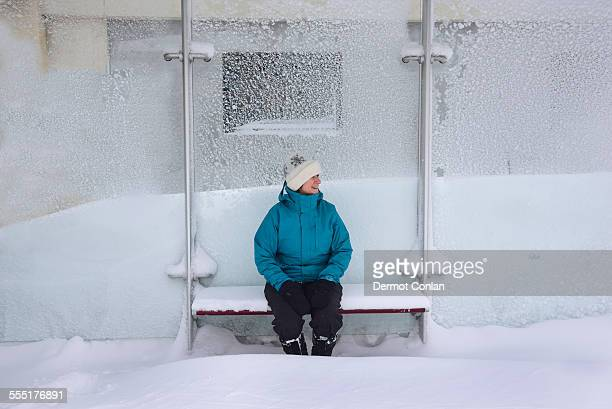 USA, Massachusetts, Boston, Middle aged woman sitting in bus stop, winter snow