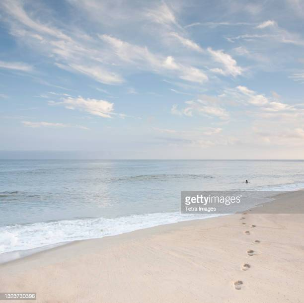 usa, massachusetts, cape cod, nantucket island, footprints on beach and woman swimming in ocean in distance - distant stock pictures, royalty-free photos & images