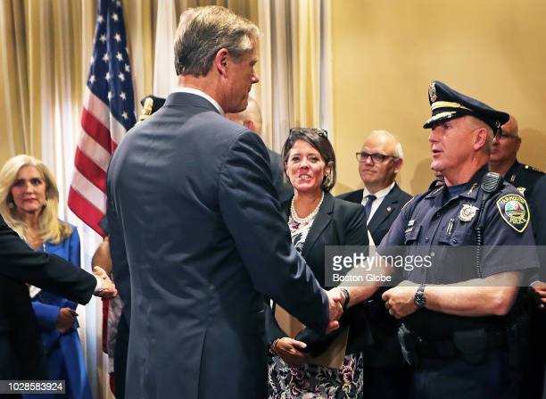Massachusetts Governor Charlie Baker shakes hands with Yarmouth Police Chief Frank Frederickson at the conclusion of a press conference to unveil new...