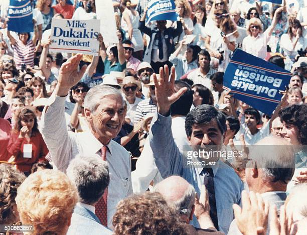 Massachusetts Governor Michael Dukakis and Texas Senator Lloyd Bentsen wave to the crowd at a campaign rally Modesto California 1988 They are...