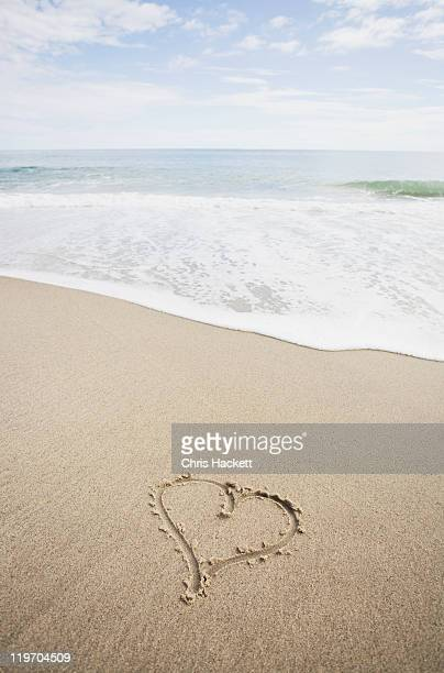 usa, massachusetts, hearts drawn on sandy beach - hackett stock photos and pictures