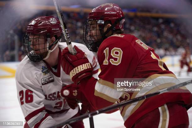Massachusetts Minutemen Defenseman Colin Felix and Denver Pioneers Forward Cole Guttman battle for the puck during the second period of the game...