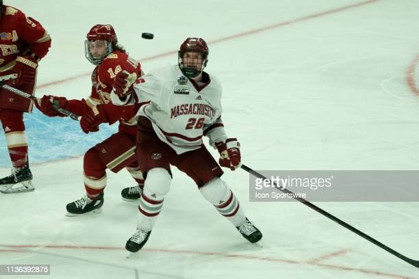 Massachusetts Minutemen Defenseman Colin Felix reaches to grab the puck with Denver Pioneers Forward Jarid Lukosevicius during the third period of...