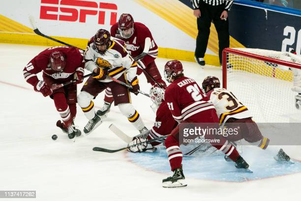 Massachusetts Minutemen Forward Jake Gaudet and Minnesota Duluth Bulldogs Forward Cole Koepke battle for the puck in front of the net with...