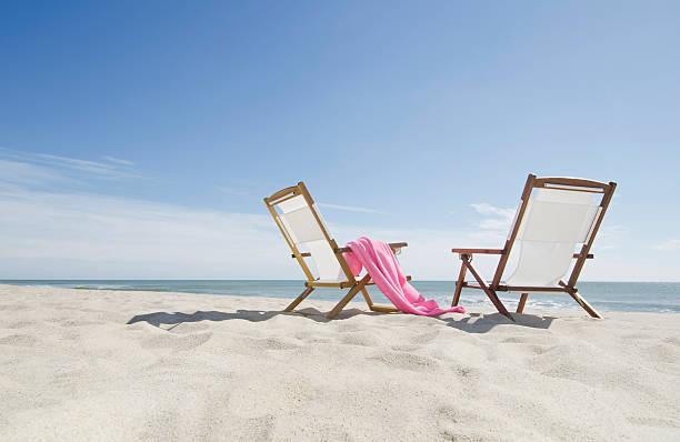 USA, Massachusetts, Nantucket, empty lounge chairs on sandy beach