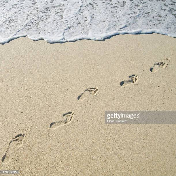 USA, Massachusetts, Nantucket, Footprints on Sandy Beach leading into sea