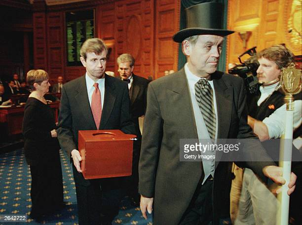 Massachusetts Secretary of the Commonwealth William Galvin center carries a ballot box containing the 12 Massachusetts electoral votes for Vice...