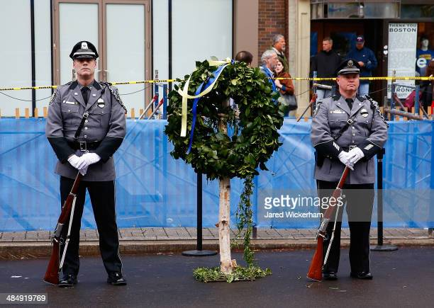 Massachusetts state and local police and fire department members stand near the site of one of the bombs following a wreathlaying ceremony...