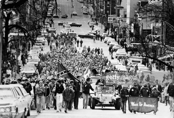 Massachusetts state representative Ray Flynn rides in a car at center in an antibusing march headed up Broadway toward Marine Park in South Boston on...