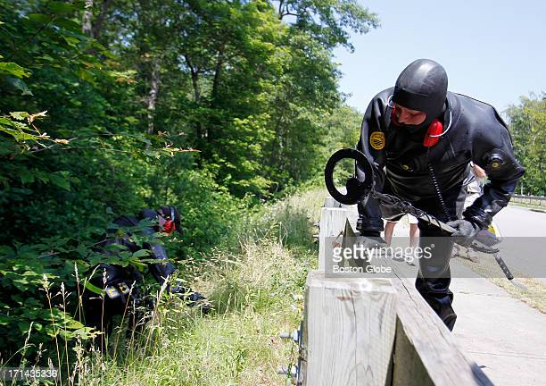 Massachusetts State Troopers search the woods along a street near Aaron Hernandez's home in North Attleborough, Mass., June 24, 2013. Hernandez, a...