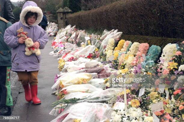 Massacre dans une école primaire de Dunblane en Ecosse Une petite fille marche à côté des fleurs déposées en hommage aux enfants tués et à leur...