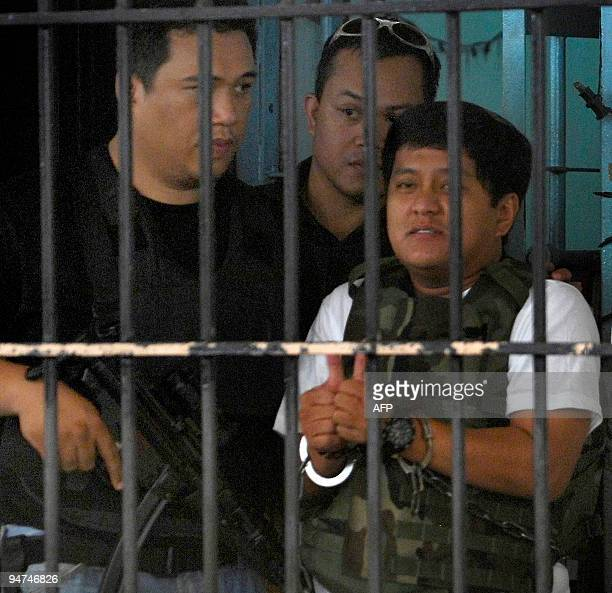 Massacre suspect Datu Unsay Mayor Andal Ampatuan gives two thumbs up as he is escorted by National Bureau of Investigation agents out of the NBI...