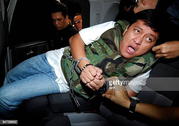 Massacre suspect Datu Unsay Mayor Andal Ampatuan is escorted by National Bureau of Investigation agents upon arriving at he Department of Justice in...
