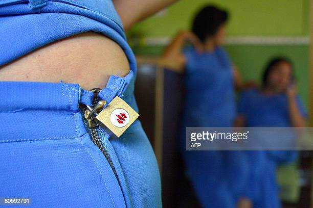 A massage girl displays her padlocked trouser while others chat beside at a parlour in Batu East Java on April 10 2008 A move by Indonesian massage...