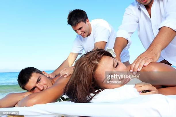 massage de couple heureux sur la plage. - massage couple photos et images de collection
