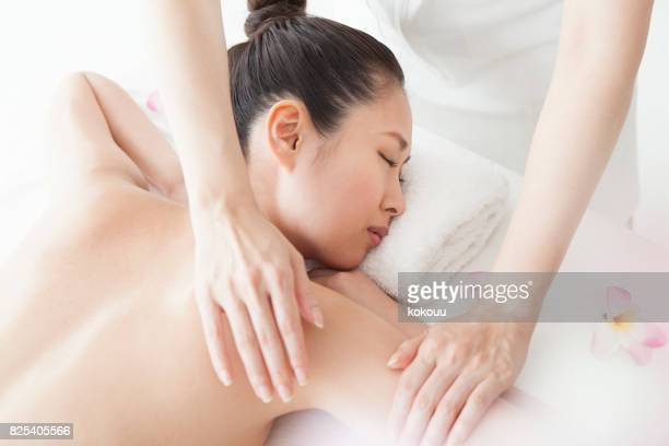 massage is given carefully around the upper arm - body massage japan stock pictures, royalty-free photos & images