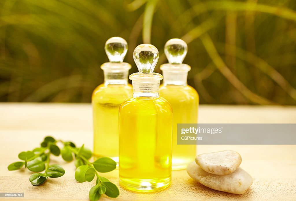 Massage oil bottles at spa with pebbles : Stock Photo