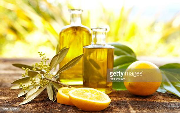 massage oil bottles with lemons and olive branch - olive oil stock pictures, royalty-free photos & images