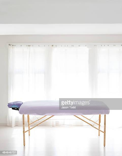 massage table in white room with curtain