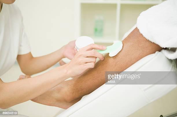Massage therapist applying depilatory