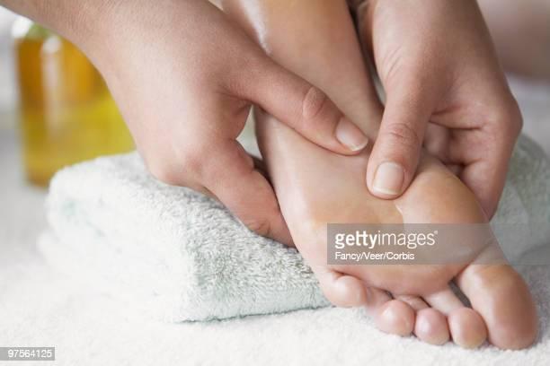 massage therapist applying pressure to foot with her thumbs - druckpunkt stock-fotos und bilder