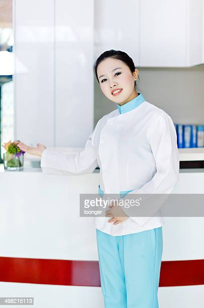 massage therapist / beautician at the front desk - medical receptionist uniforms stock photos and pictures