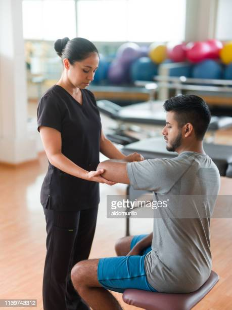 massage therapist checking patient's arm - sports medicine stock pictures, royalty-free photos & images
