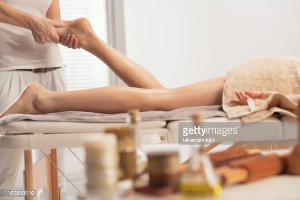 massage therapist doing foot massage - healing massage. woman enjoying in relaxing massaging at health spa treatment - massaggio sensuale foto e immagini stock