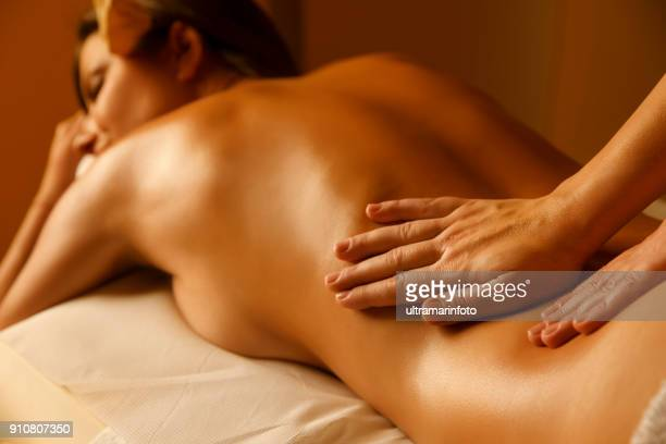 massage therapist doing healing massage. woman enjoying in relaxing massaging at health spa treatment. - sensual massage stock photos and pictures